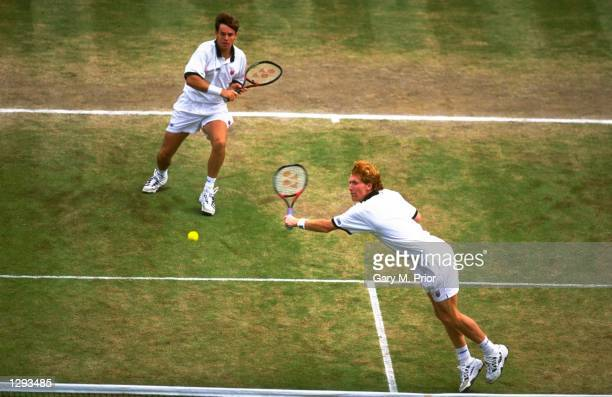 Todd Woodbridge and double partner Mark Woodforde of Australia in action during the 1998 Wimbledon Championships played at Wimbledon London England...