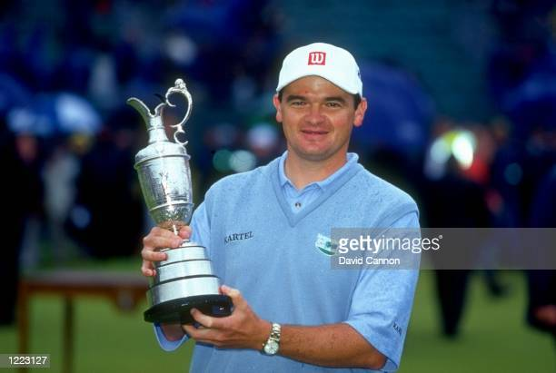 A portrait of Paul Lawrie of Scotland holds the British Open trophy after winning the event played at the Carnoustie GC in Carnoustie Scotland...
