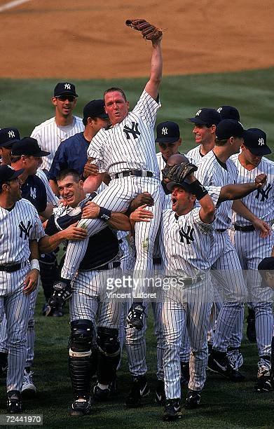David Cone of the New York Yankees celebrates as his teammates lift him after winning the game against the Montreal Expos at Yankee Stadium in Bronx...
