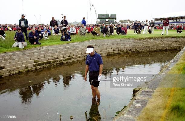 Jean Van De Velde of France looks at his ball in the burn on the 18th hole during the British Open played at the Carnoustie GC in Carnoustie Scotland...