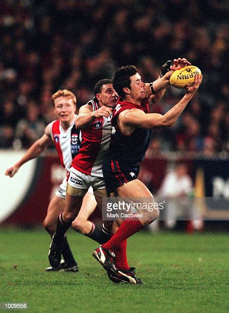 Matthew Young looks on as Tony Francis for St Kilda attempts to spoil Adem Yze for Melbourne during the round seventeen match of the Australian...