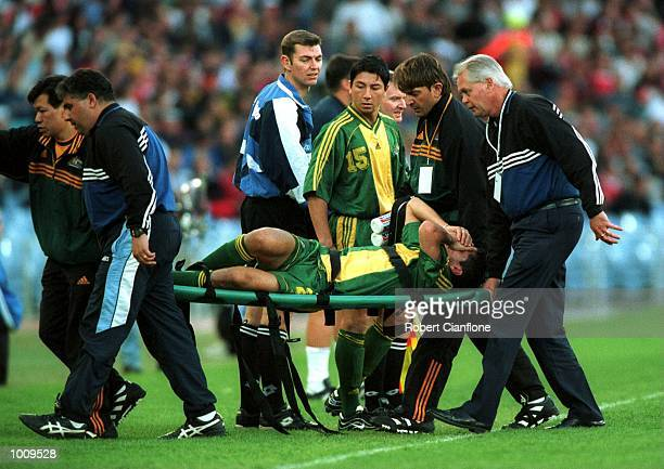 Simon Colosimo of Australia is stretchered off with damaged knee ligaments after being fouled by Andy Cole of Manchester United during the Sharp...