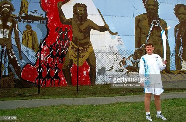 Ann Dixon stands in front of a Aboriginal mural in Preston while taking part in the torch relay Mandatory Credit Darren McNamara/ALLSPORT