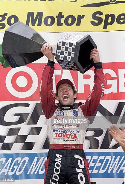Driver Cristiano da Matta of Brazil who drives the Toyota Reynard 2KI for PPI Motorsports raises his trophy after winning first place in the Target...