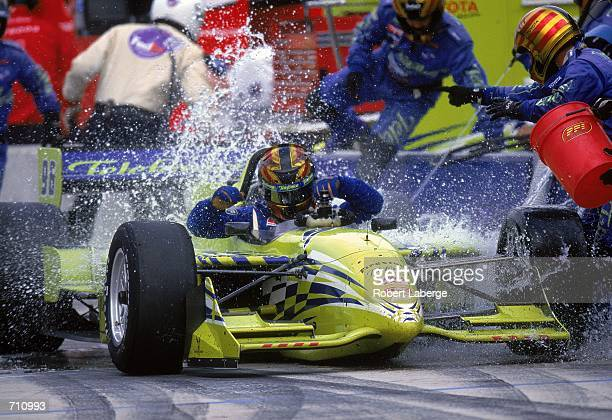 Driver Orel Servia of Spain who drives the Toyota Reynard 2KI for PPI Motorsports is doused with water as he car catches fire in the pit during the...