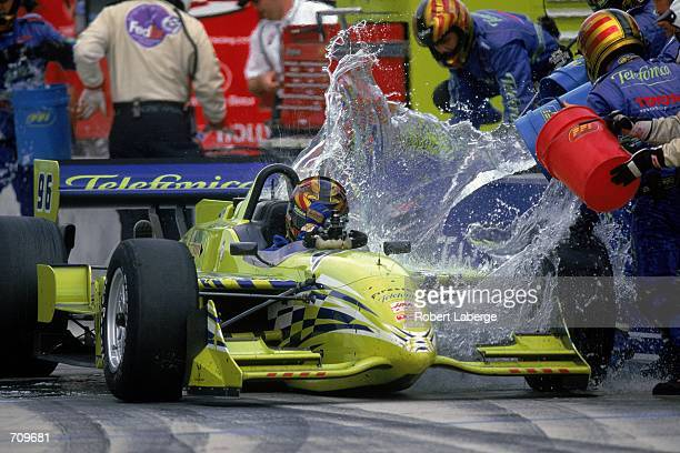 Driver Oriol Servia of Spain who drives a Toyota Reynard 2KI for PPI Motorsports is getting doused with water during a pit fire at the Target Grand...