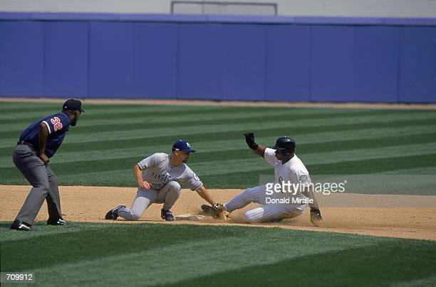 Frank Thomas of the Chicago White Sox slides into base as Umpire Chuck Meriwether watches Jeff Reboulet of the Kansas City Royals try to tag during...