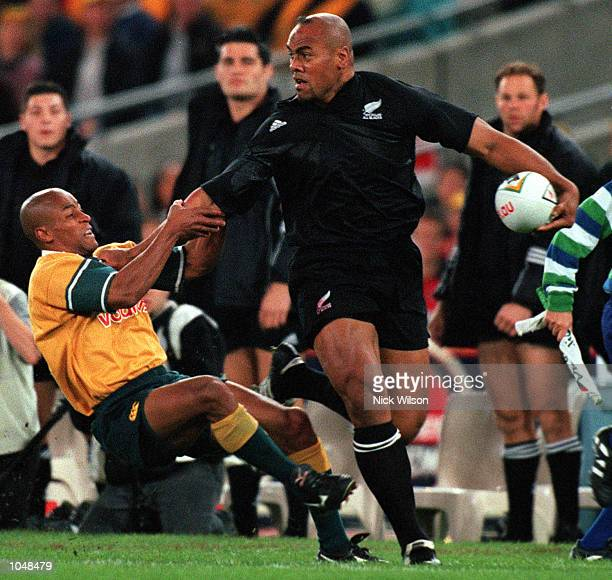George Gregan of Australia falls of Jonah Lomu of New Zealand during the match between Australia v New Zealand for the Bledisloe Cup at Stadium...