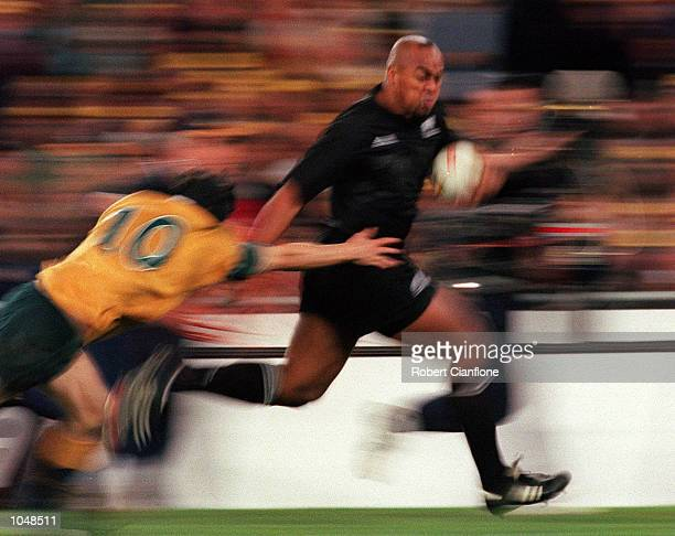 Jonah Lomu of New Zealand evades the tackle of Stephen Larkham of Australia during the match between Australia v New Zealand for the Bledisloe Cup at...