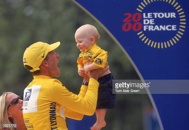 Lance Armstrong of the USA and the US Postal team celebrates winning race with son Luke after completing the final Stage 21 between Paris and the...