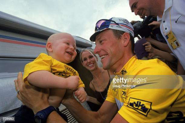 Lance Armstrong of the USA who rides with the yellow shirt for the US Postal Service Team is holding his son Luke with his wife Kristin looking on...