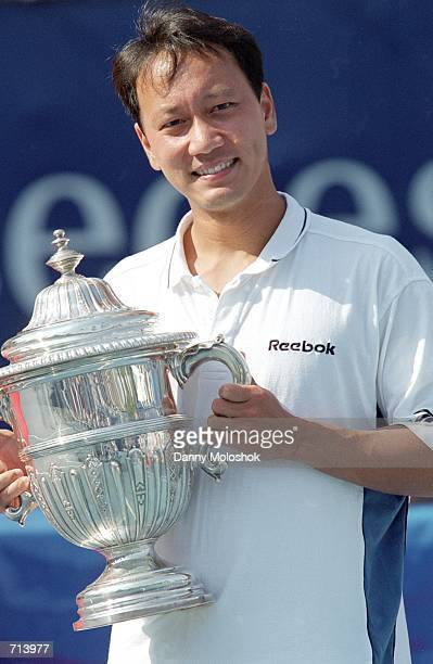 Michael Chang smiles as he poses with the trophy after winning the match against JanMichael Gambill by default at the MercedesBenz Cup part of the...