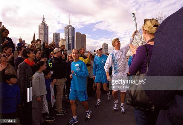 Rob Woodhouse member of the Mean Machine swimming team carries the Olympic Torch through a crowd at Southbank Melbourne Australia Mandatory Credit...