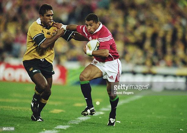 Jason Robinson of the Lions hands off Andrew Walker of Australia during the Second Test Match between the Australian Wallabies and the British and...