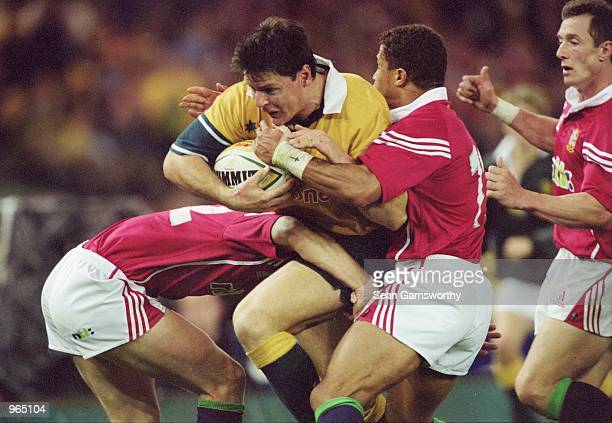 Matt Burke of Australia is tackled by Rob Henderson and Jason Robinson of the British Lions during the British and Irish Lions tour match against...
