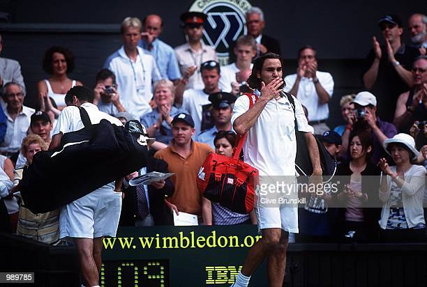 Roger Federer of Switzerland blows a kiss to the fans as Pete Sampras of the USA walks off court during the men's fourth round of The All England...