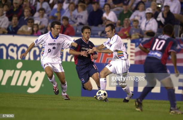Shaker Asad of the New England Revolution tries to dribble through the defense of Kerry Zavagnin and Mike Burns of the Kansas City Wizard during the...