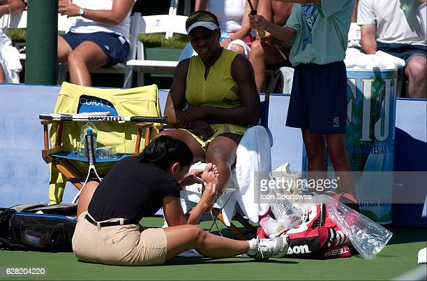 Serena Williams and a trainer tend to a blister on her foot during her match versus Jelena Jankovic during the Acura Classic at La Costa Resort and...