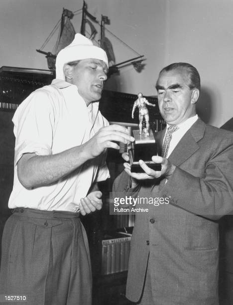 Bert Trautmann Manchester City's German goalkeeper who broke his neck during the FA Cup Final against Birmingham is seen showing his Player of the...
