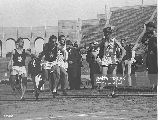 Athletes hand over batons during a 4x440 relay event between University of Southern California and Stanford in the Coliseum Stadium Los Angeles USA...