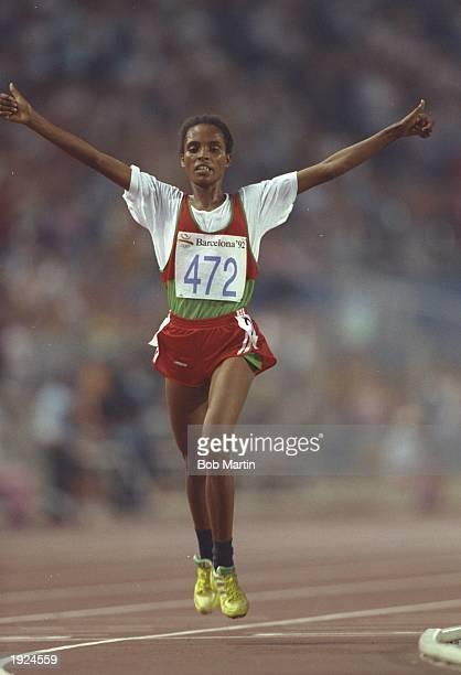 Derartu Tulu of Ethiopia holds her arms aloft as she crosses the line to win the 10000 metres event during the 1992 Olympic Games at the Monjuic...