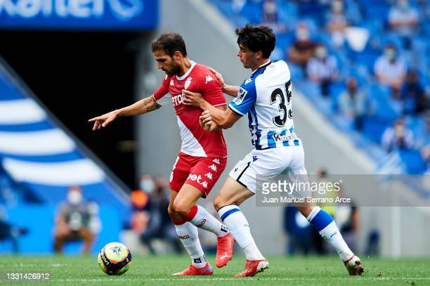 Julen Lobete of Real Sociedad duels for the ball with Cesc Fabregas of AS Monaco during the Friendly Match between Real Sociedad and As Monaco at...