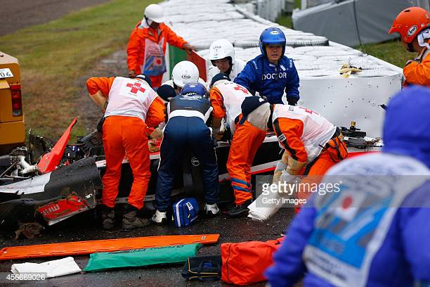 Jules Bianchi of France and Marussia receives urgent medical treatment after crashing during the Japanese Formula One Grand Prix at Suzuka Circuit on...