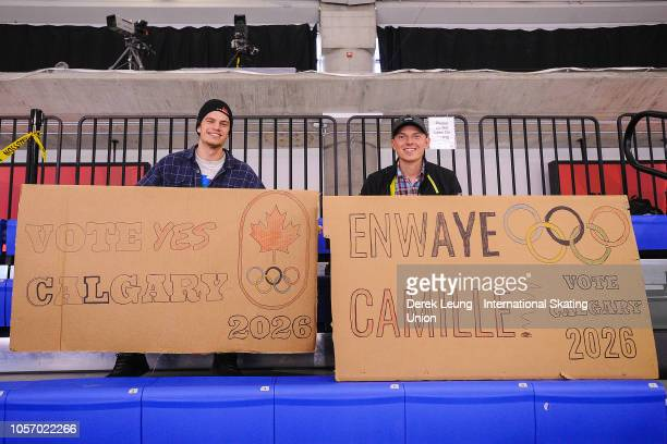 Jules Burnotte of Sherbrooke Quebec and Pearce Hanna of Canmore Alberta hold up signs encouraging Calgary's 2026 Olympic bid during the ISU World Cup...