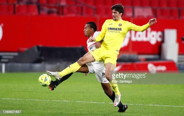 Jules Koundé of Sevilla and Gerard Moreno of Villarreal compete for the ball during the La Liga Santander match between Sevilla FC and Villarreal CF...