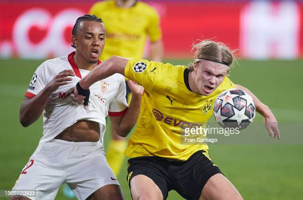 Jules Kounde of Sevilla FC competes for the ball with Erling Haaland of Borussia Dortmund during the UEFA Champions League Round of 16 match between...