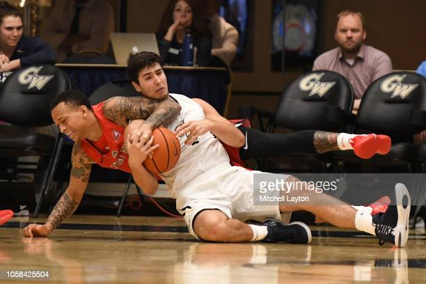 Jules Moor of the Stony Brook Seawolves and Adam Mitola of the George Washington Colonials fight for loose ball during a college basketball game at...