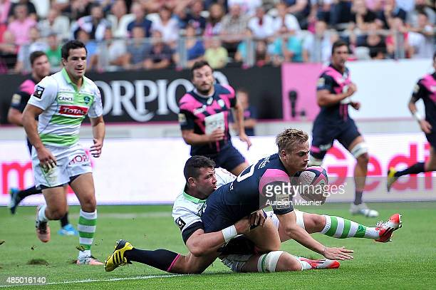Jules Plisson of Stade Francais is being tackled during the Top 14 game between Stade Francais and Pau at Stade Jean Bouin on August 23, 2015 in...