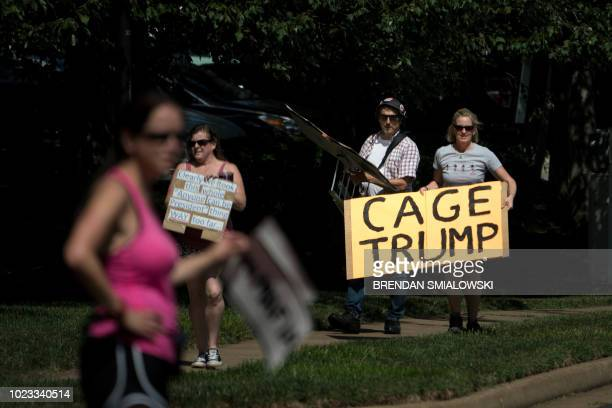 Juli Briskman carries a sign with others to protest as US President Donald Trump leaves the Trump National Golf Club in Sterling Virginia to return...