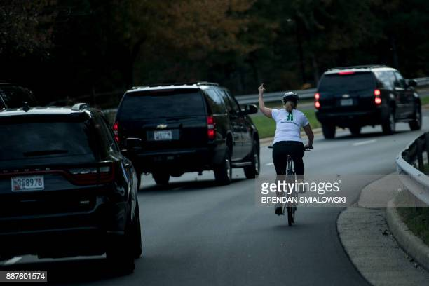 TOPSHOT A woman on a bike gestures with her middle finger as a motorcade with US President Donald Trump departs Trump National Golf Course October 28...