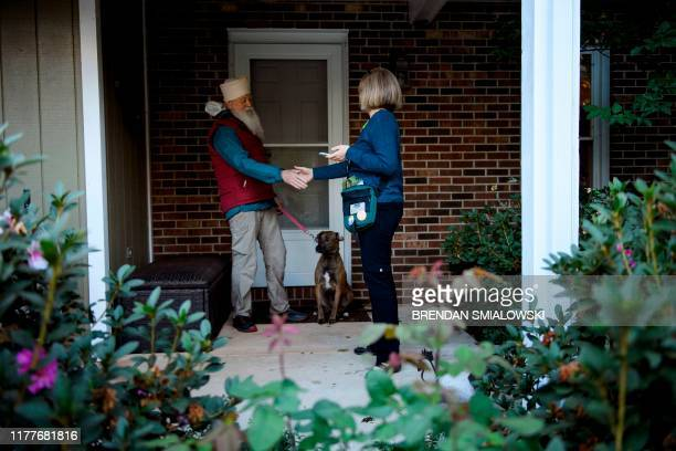 Juli Briskman who was fired after giving US President Donald Trump's motorcade the middle finger while cycling in 2017 greets a voter while...