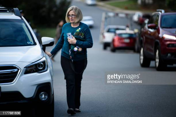 Juli Briskman who was fired after giving US President Donald Trump's motorcade the middle finger while cycling in 2017 walks from her car while...