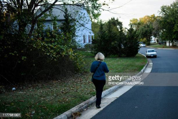 Juli Briskman who was fired after giving US President Donald Trump's motorcade the middle finger while cycling in 2017 walks to homes while...