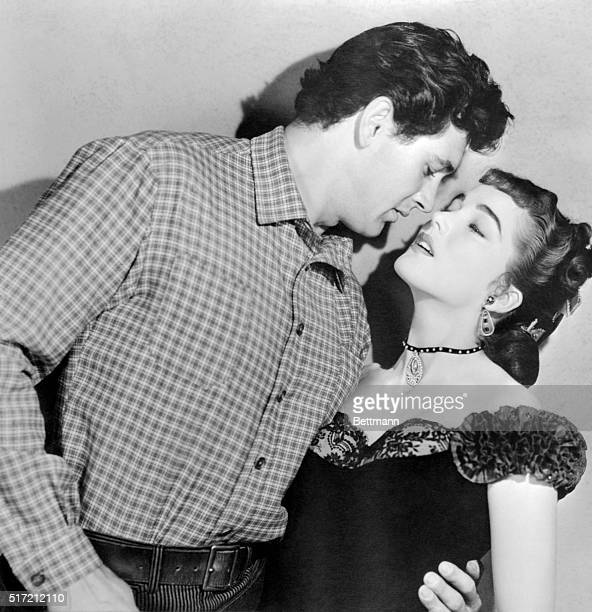 Julia Adams may be wearing yesterday's gowns but she dishes up today's kisses here Rock Hudson who sampled her smooching in The Lawless Breed said...