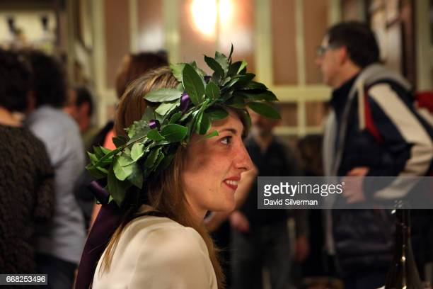 Julia an Italian veterinary student wears a symbolic laurel wreath as she celebrates her graduation with friends at the Osteria Del Sole bar on March...
