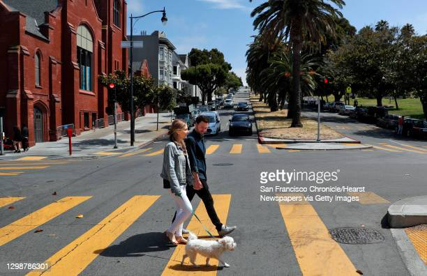 Julia and Jack Altman walk with their rescue dog Teddy in Dolores Park near their home in the Mission District of San Francisco, Calif., on Sunday,...