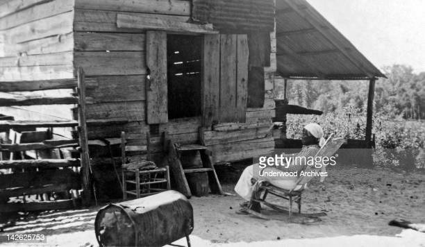 Julia Ann Jackson, age 102, and the corn crib where she lives, late 1930s. She uses the large battered tin can for a stove and does her cooking on...