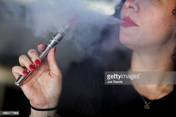 Julia Boyle enjoys an electronic cigarette as she waits for customers at the Vapor Shark store on April 24 2014 in Miami Florida Brandon Leidel CEO...
