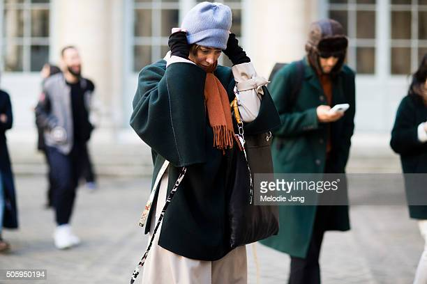 Julia Butault exits the Lemaire show in a green oversized Celine sweater coat tan Margiela dress baby blue beanie hat and a black leather tote and...
