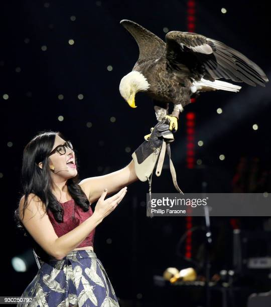 Julia Cecere holds a bald eagle named Challenger as the American national anthem is performed at Celebrity Fight Night XXIV on March 10 2018 in...