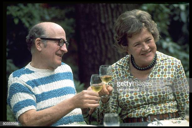 Julia Child and husband Paul Child enjoying a convivial wine toast in outdoor setting