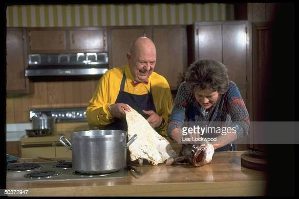 Julia Child and James Beard laughing while cleaning a large fish on TV show Revolutionary Recipes