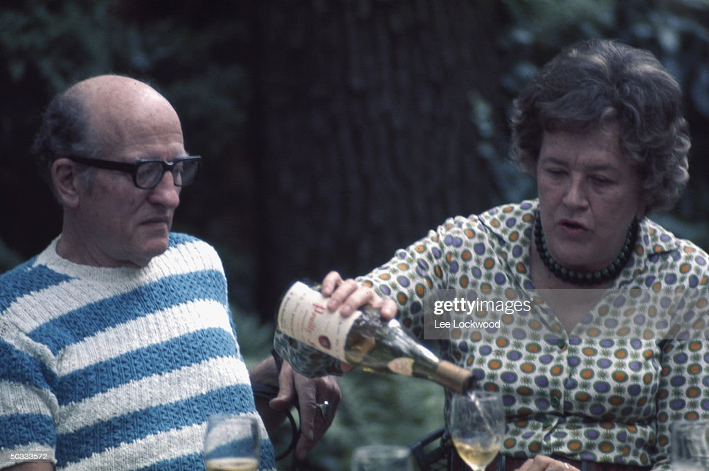 Julia Child (L), in outdoor setting, pouring wine with husband, Paul Child, observing.