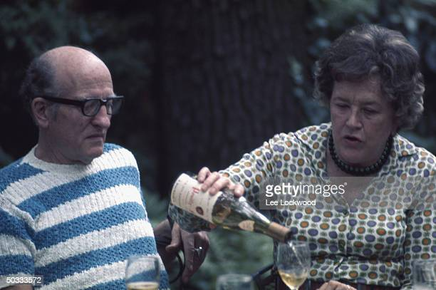 Julia Child in outdoor setting pouring wine with husband Paul Child observing