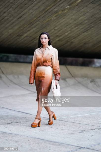 Julia Comil wears a brown and beige bi-color leather oversized shirt with long sleeves, a slit skirt, brown high heeled leather shoes, a white...