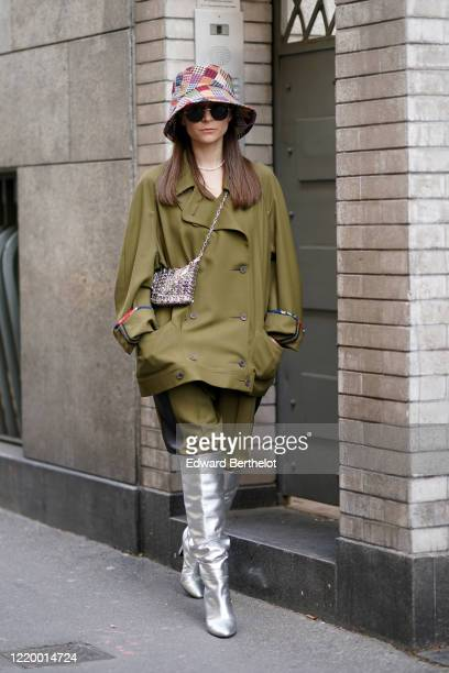 Julia Comil wears a colorful checked bob hat, a green khaki oversized pullover, pants, silver pointy high heel high boots, outside Etro, during Milan...